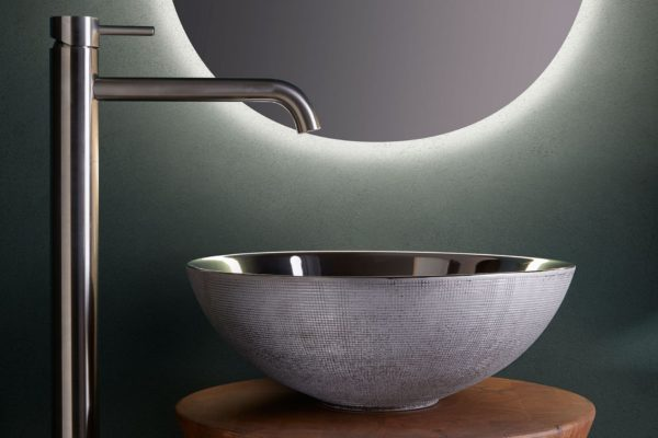Gray stainless steel basin on a wooden circular stool under a stainless steel tap